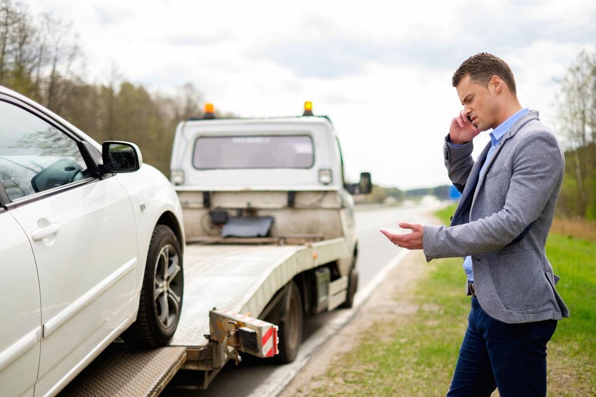 kierowca z telefonem przy aucie ładowanym na lawetę