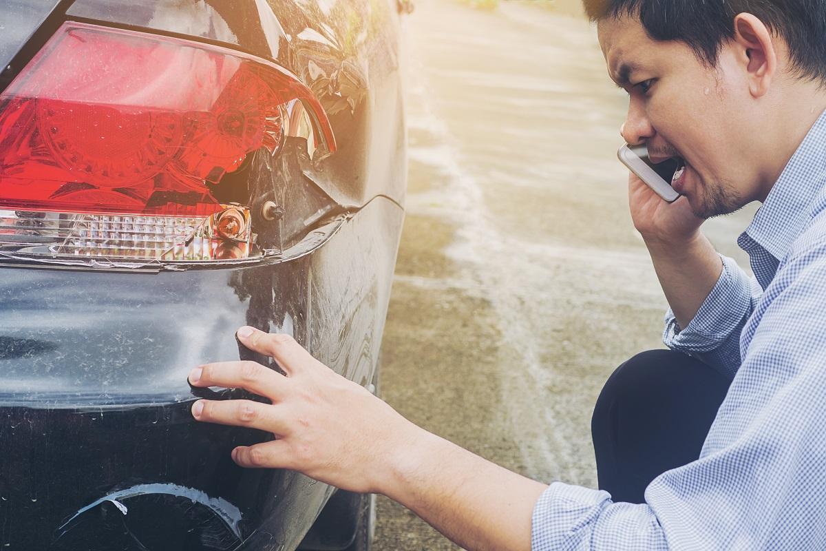 kierowca z telefonem przy rozbitej lampie auta