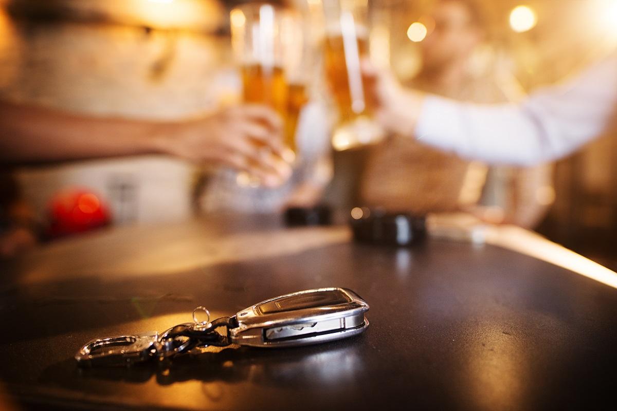 kluczyki od auta na stole a tle alkohol